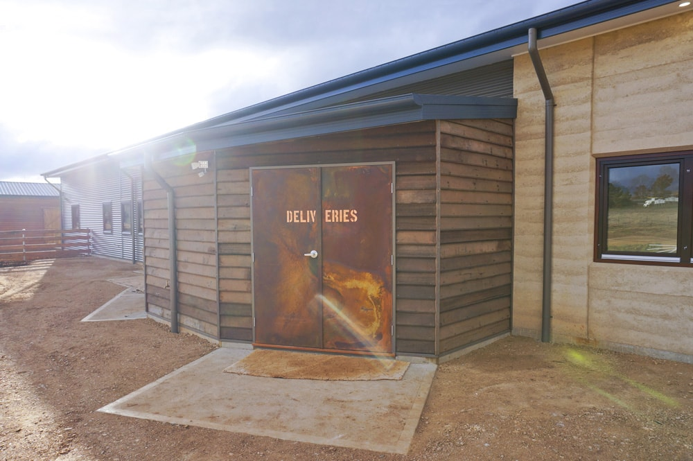 Rustic copper and coreten steel 'deliveries' door on a Rammed Earth building. Vet hospital by Architecture Republic, Bowral
