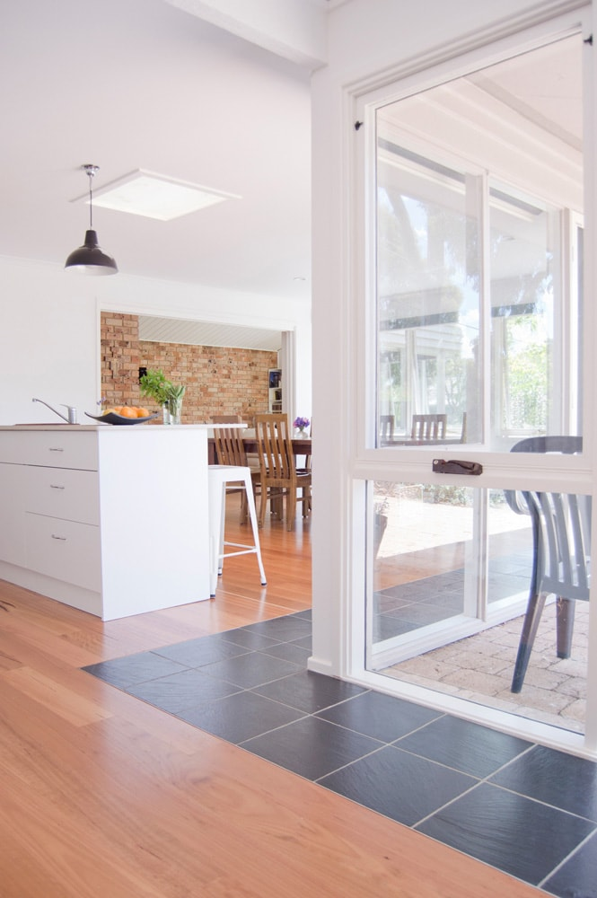 Slate and timber floors underneath north facing windows of a kitchen and living space. Designed by Architecture Republic.
